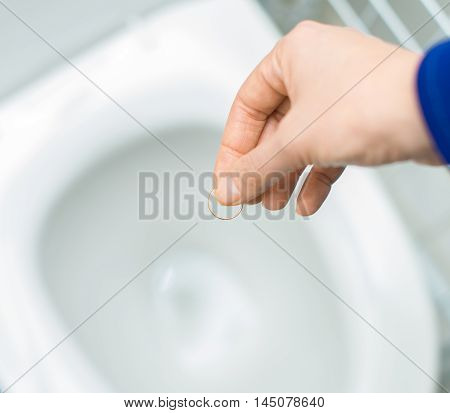 Divorce Concept. Woman Throwing Her Wedding Ring In The Toilet.