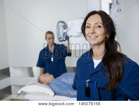 Radiologist Smiling While Colleague Taking Patient's Xray