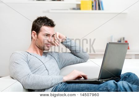 Smiling young man working on laptop at home copy space