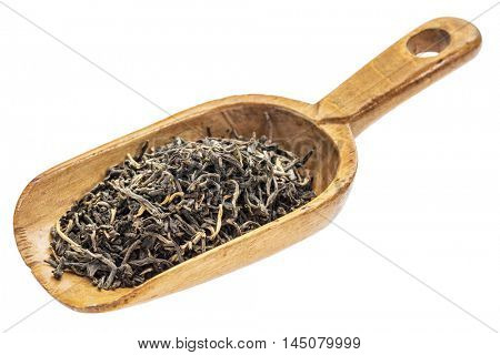 loose leaf black tea on a rustic wooden scoop, isolated on white