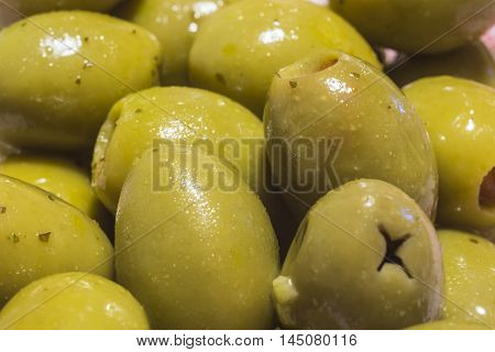 Cutting narrow green olives already pitted Italian