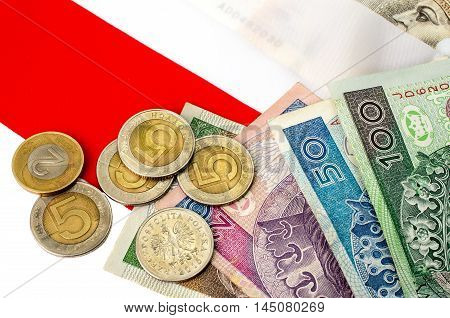 Polish zloty. Many banknotes and coins of different denomination and the Polish flag.