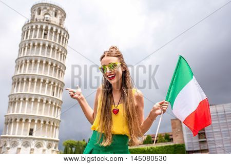 Young female traveler with atalian flag near the famous leaning tower in Pisa old town in Italy. Happy vacations in Italy