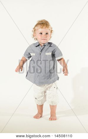 Beautiful little kid standing in equilibrium for his first steps isolated on white background, little sepia toning