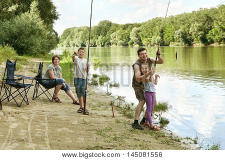 people camping and fishing, family active in nature, child caught fish on bait, river and forest, summer season