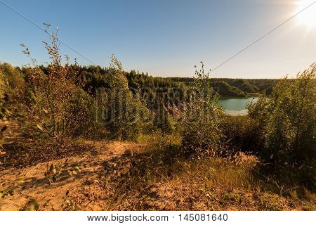 Quarry Or Lake Or Pond With Sandy Beach, Green Water, Trees And Hills With Blue Sky