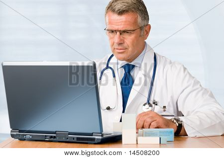 Mature doctor working on laptop and medication's cases to make prescriptions in his clinic office