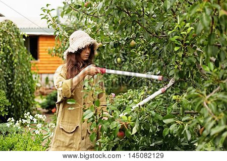 Cute girl with long hair makes large cutting garden garden scissors. She is wearing a straw hat and work clothes.