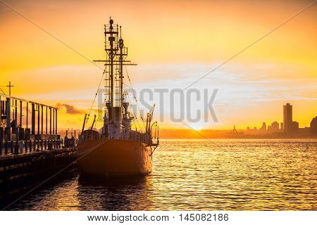 Cargo ship in the harbor at commercial port at sunset time. Sun is going down against beautiful sky at the dock with mooring vessel.