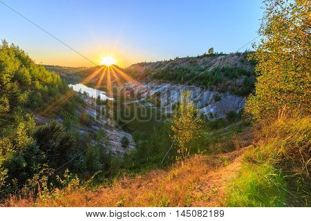 Sunset Quarry Or Lake Or Pond With Sandy Beach, Green Water, Trees And Hills With Blue Sky