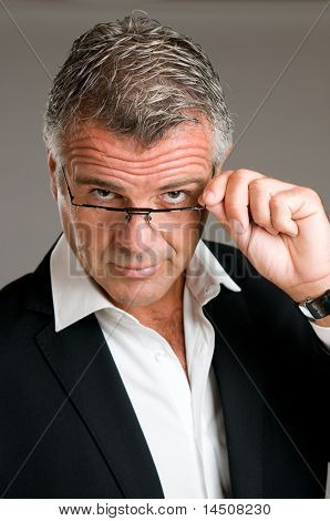 Mature man holding and putting on a pair of glasses with satisfaction