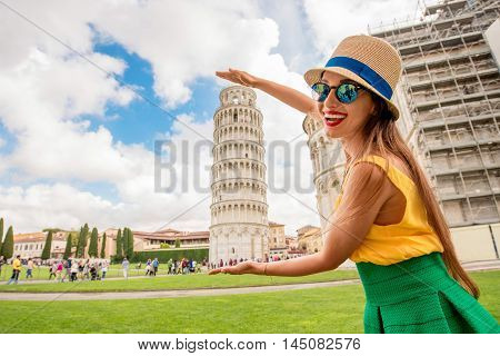 Young female traveler having fun in front of the famous leaning tower in Pisa old town in Italy. Happy vacations in Italy