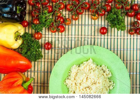 Selection of ingredients for cooking couscous: tomatoes, couscous, herbs, peppers; top view