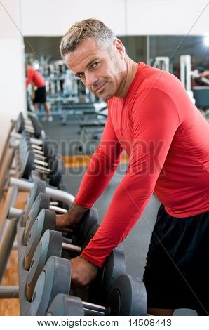 Satisfied mature man picks up dumbbells from the rack at gym