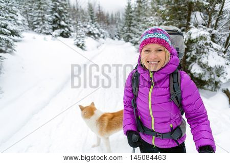Woman hiking in white winter forest woods with akita dog. Young girl walking on snowy trail. Recreation fitness and healthy lifestyle outdoors in nature. Motivation and inspirational winter landscape.
