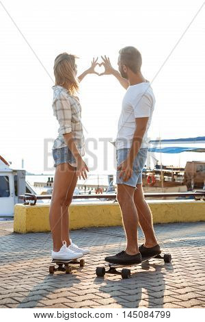 Young beautiful couple walking at seaside, showing heart, skateboarding. Outdoor background.