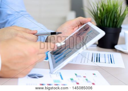 Business colleagues working and analyzing financial figures / graphs on a digital tablet