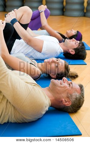 Happy fitness people in a row doing some aerobic stretching after workout at gym