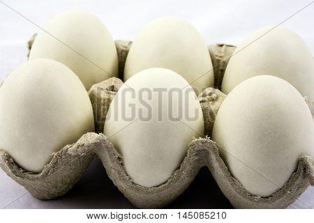 half dozen white eggs in grey cardboard carton