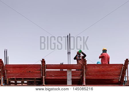 MANAMA, BAHRAIN - AUGUST 27, 2016: Construction workers taking a break on a high rise building site in the Capital City of the Kingdom.