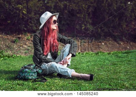 Beautiful stylish red haired fashion hipster model woman sitting outdoors on green grass at park wearing sunglasses hat and black leather coat.