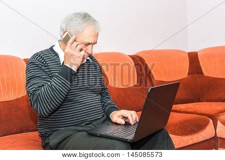 Senior businessman talking on cell phone and typing on laptop sittin on sofa. Concept photo of senior people and modern technology.