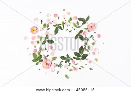 Floral round frame with rose flowers petals red berries and green leaves on white background. Flat lay top view