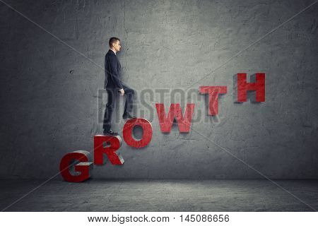 Side view of a businessman walking up ladder made of letters that arrange 'growth' word. Development and upsurge. Success and progress.