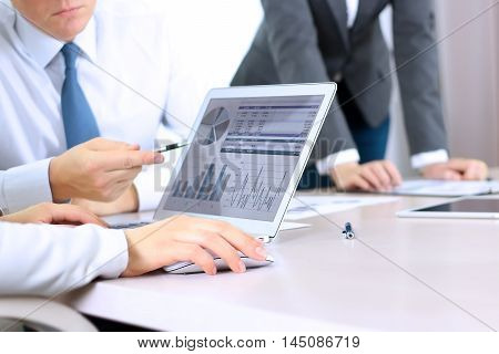 Business colleagues working and analyzing financial figures / graphs on a digital laptop