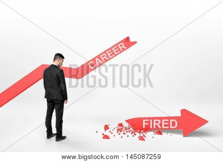 Back view of a businessman looking at broken arrow with 'fired' word that fall off the graph with 'career' word. Financial problems and troubles. Losing a job. Dismissing and discharging.