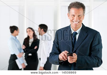 Happy smiling mature businessman receiving positive news on his smart phone at office
