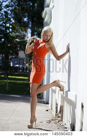 Portrait in full growth, Beautiful young blonde woman in orange dress, against white wall, summer outdoors