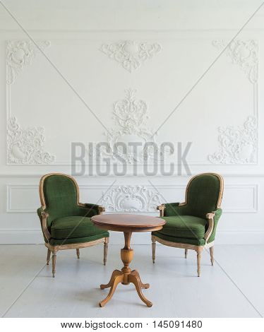 portrait of vintage vanity table set with stool over wall design bas-relief stucco mouldings roccoco elements.