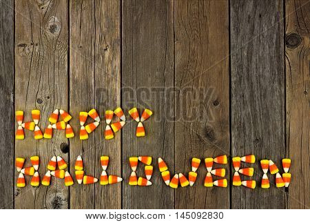Happy Halloween Written With Candy Corn Over A Rustic Wooden Background