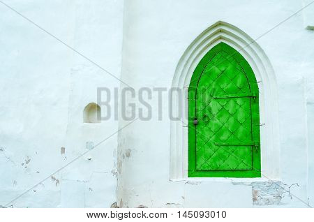 Architecture view of architecture details - old green metal forged door with arcade on the white stone wall. Architecture background.
