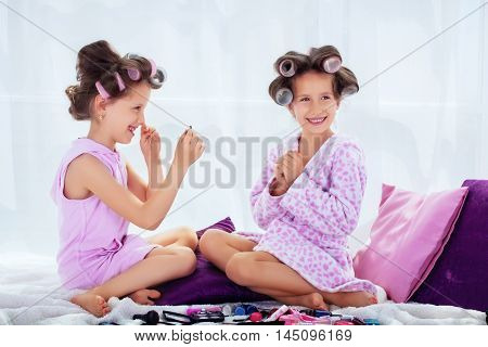 happy children in curlers do hair and makeup