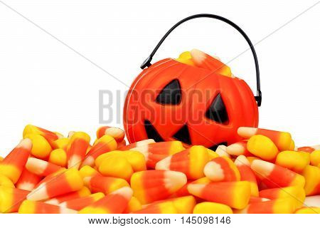 Small Halloween Jack O Lantern Pail Behind A Large Pile Of Candy Corn Over A White Background