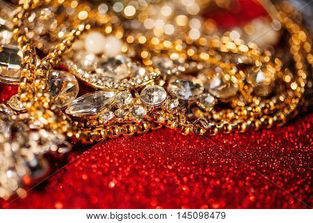 Collection of assorted gemstone jewellery on red shiny glitter background