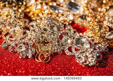 Close up of collection of assorted golden and silver jewellery on red shiny background
