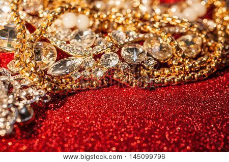 Close up of collection of assorted precious jewellery on red shiny glitter background