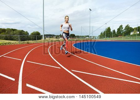 Full length of determined woman running on sports tracks