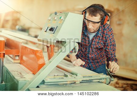 Carpenter at work.Carpenter checking if everything is functioning as it should in his workshop.