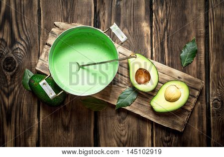 The guacamole and greens on the Board on wooden background.
