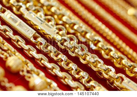 Gold necklace on red cloth background closeup
