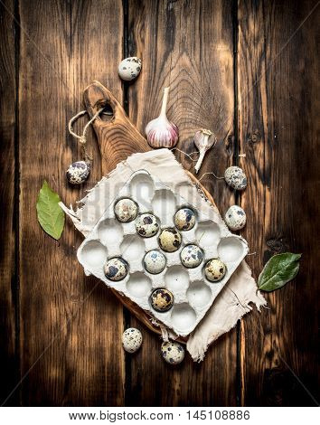 Quail eggs in a box with Laurel leaves. On a wooden table