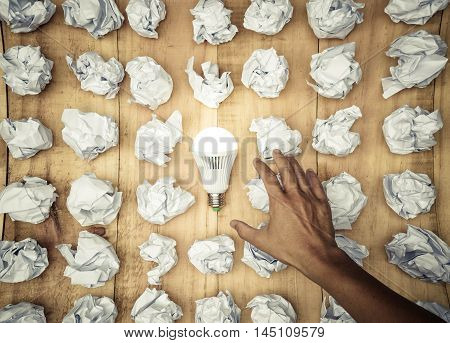 Hand trying to catch a turned on LED light bulb surrounded by crumpled paper ball / Business with new bright ideas and innovation concept