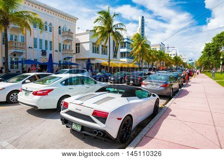 MIAMI BEACH, USA - AUGUST 27, 2016 : Tourists and luxury cars  at Ocean Drive, a popular tourist destination and home of several famous hotels, restaurants and discos in South Beach