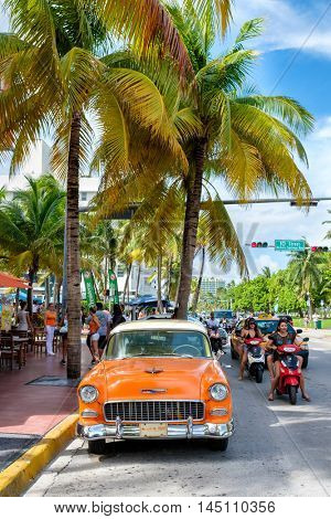 MIAMI BEACH, USA - AUGUST 27, 2016 : Vintage car and people at Ocean Drive, a popular tourist destination and home of several famous hotels, restaurants and discos in South Beach