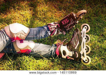 Legs in roller skates and protection on the grass. Toned in bright sunny colors
