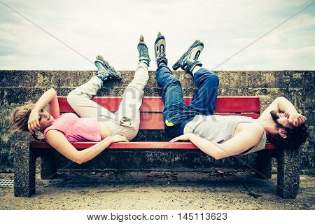 Young tired people friends with roller skates. Woman and man relaxing lying on bench outdoor.